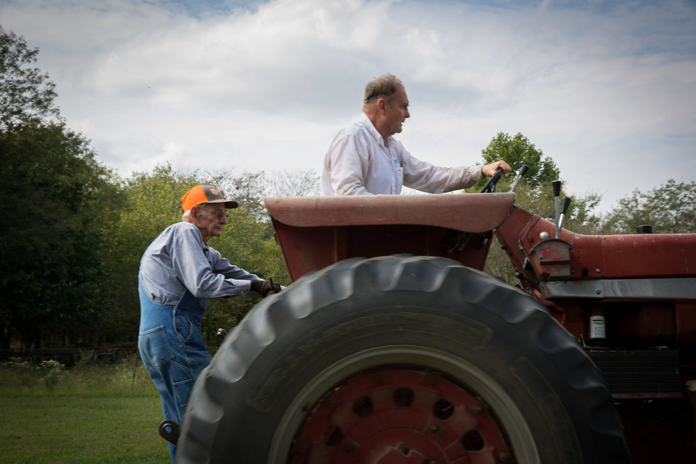 Carl hitches a ride as Mike drives the tractor to the grain silo they are cleaning out for the corn harvest.