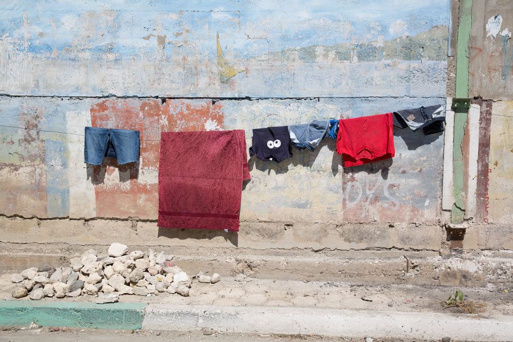 Laundry hangs along Rue Du Commerce in Jacmel, Haiti, on Feb.4, 2018. Without washing machines, washing clothes by hand at the river or at home is a regular chore for many Haitian women and girls.