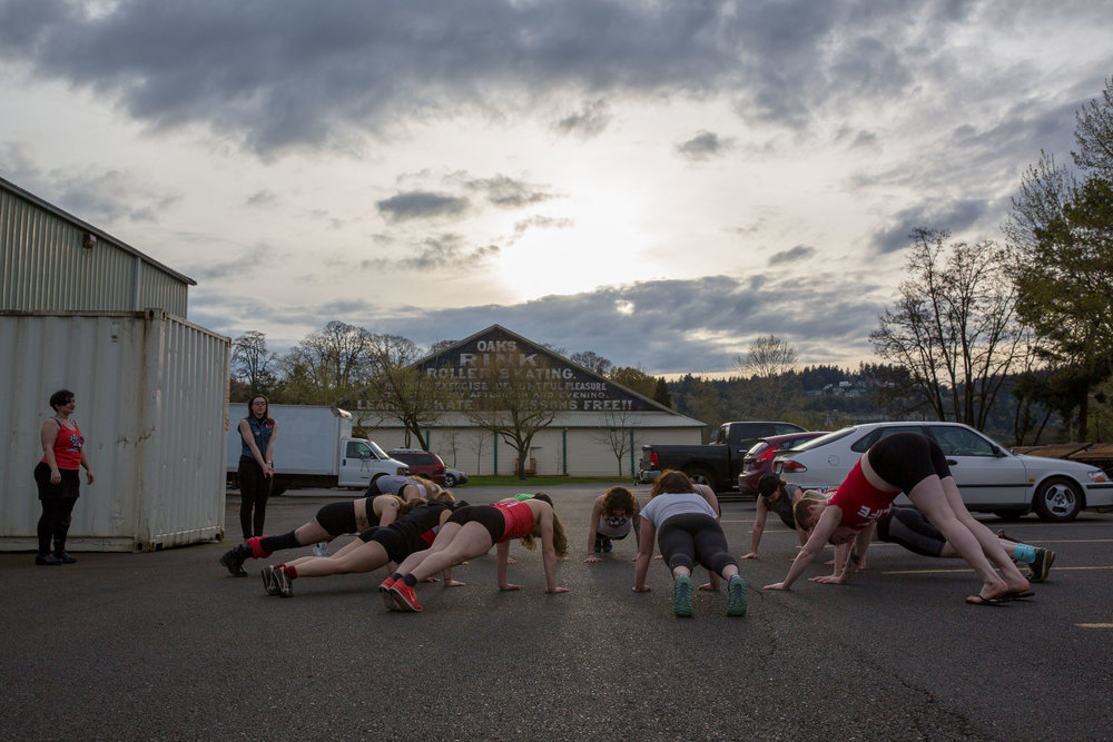 The Break Neck Betties, one of the RCR competitive women's teams, take advantage of a mild evening and do some pre-game exercises outside the Oaks Park Hangar in Portland, Ore. on April 4, 2018.