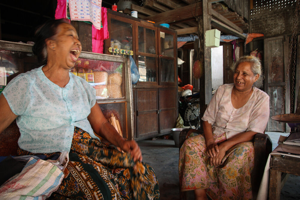 Two women who have been friends for 50 years laugh together on a hot afternoon in their shop in Hsipaw, Burma, June, 2014.