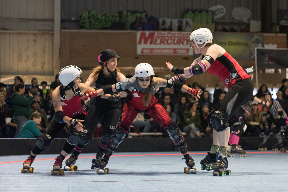 Smelter Skelter (center) and Betties teammates block Guns N Rollers skater during a game on May 13, 2017. Guns N Rollers defeated the Break Neck Betties 226-222.