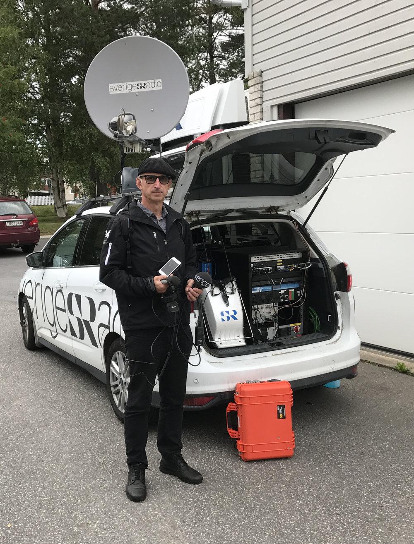 Anders Wikström, länsreporter på SR Västerbotten, framför en av satellitbilarna. Notera den orangea Minilänk-väskan och den vita HF-ryggsäcken som sänder analogt från reporter till bil, vidare över IP med satellitlänken.
