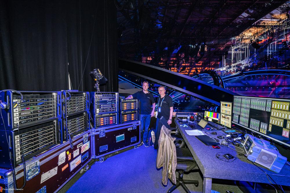"""– Det här är vad vi kallar för den trådlösa världen, säger Volker och pekar mot racken: """"På vänstra sidan har vi mottagarna i 6000-serien, och på högersidan sändarna i 2000-serien."""" I bakgrunden skådas Sennheisers Jonas Naesby (t.v.) tillsammans med kollegan Gerhard Spyra. / Foto: Ralph Larmann"""