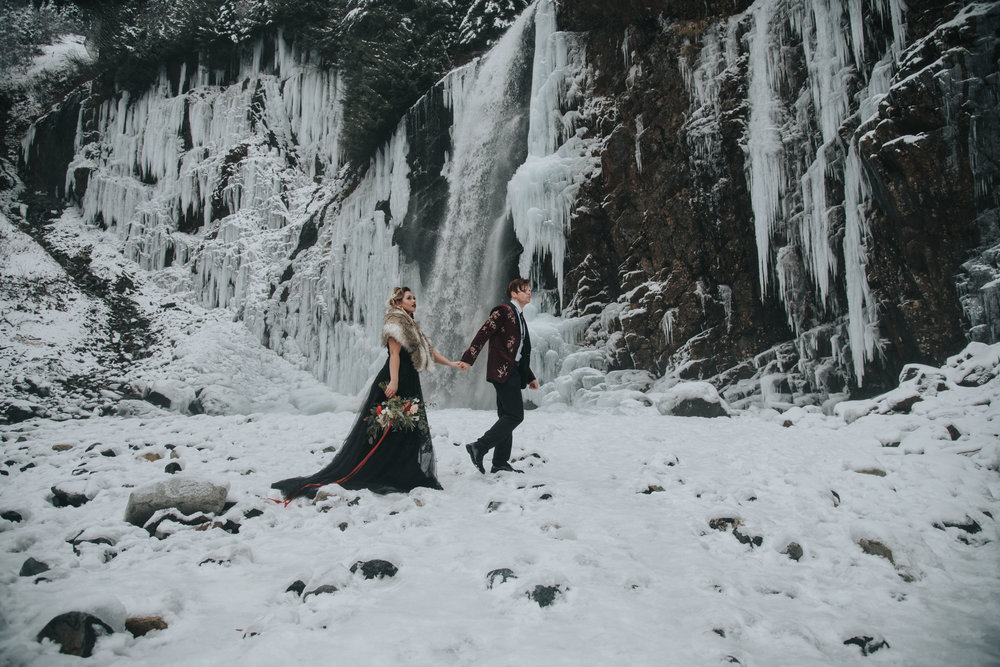 A bride in a black wedding gown and her groom traverse a wintery landscape during their winter elopement.