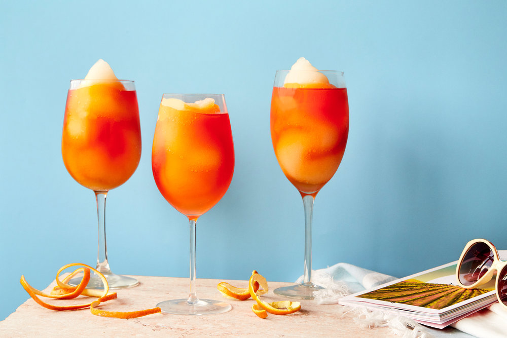 Three Frozen Aperol Spritz slushy drinks on a table.