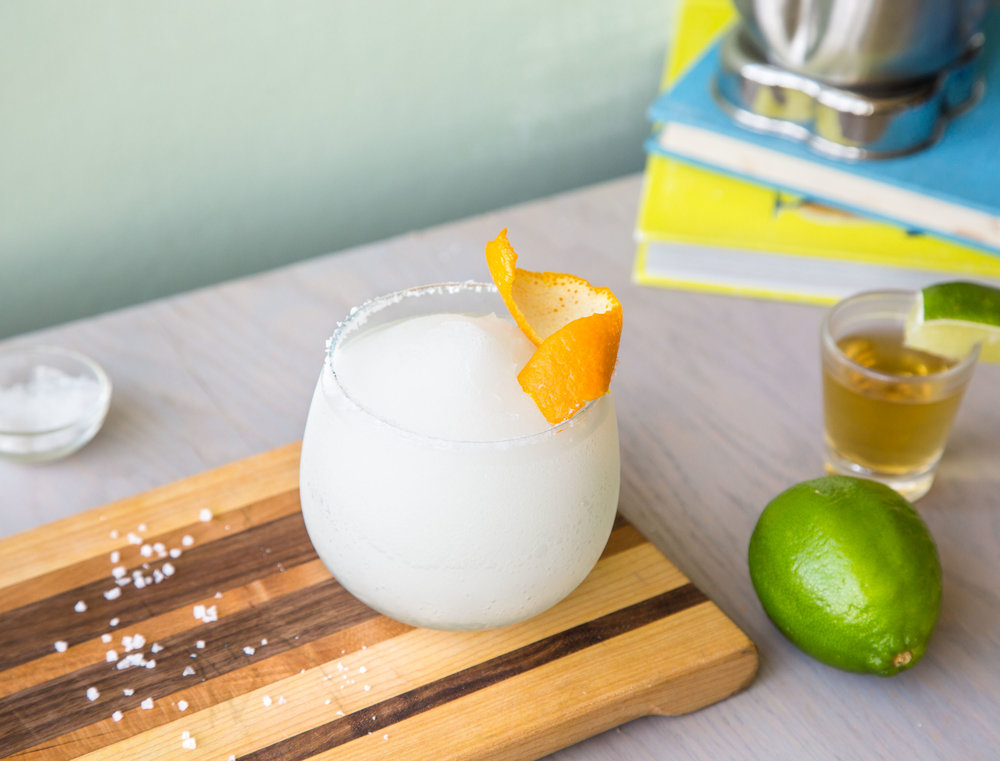 Frozen margarita in a glass, on a cutting board, and with fresh orange.