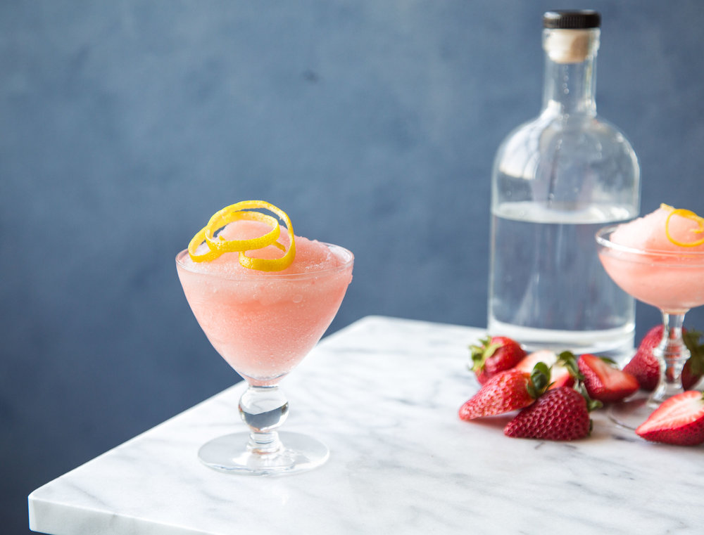 Frozen Strawberry Fields drink in a glass with a fresh lemon wedge on top.