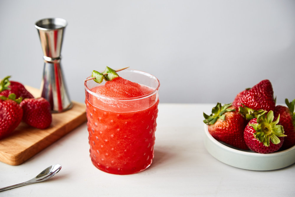 Frozen Strawberry Daiquiri in a glass next to some fresh strawberries.