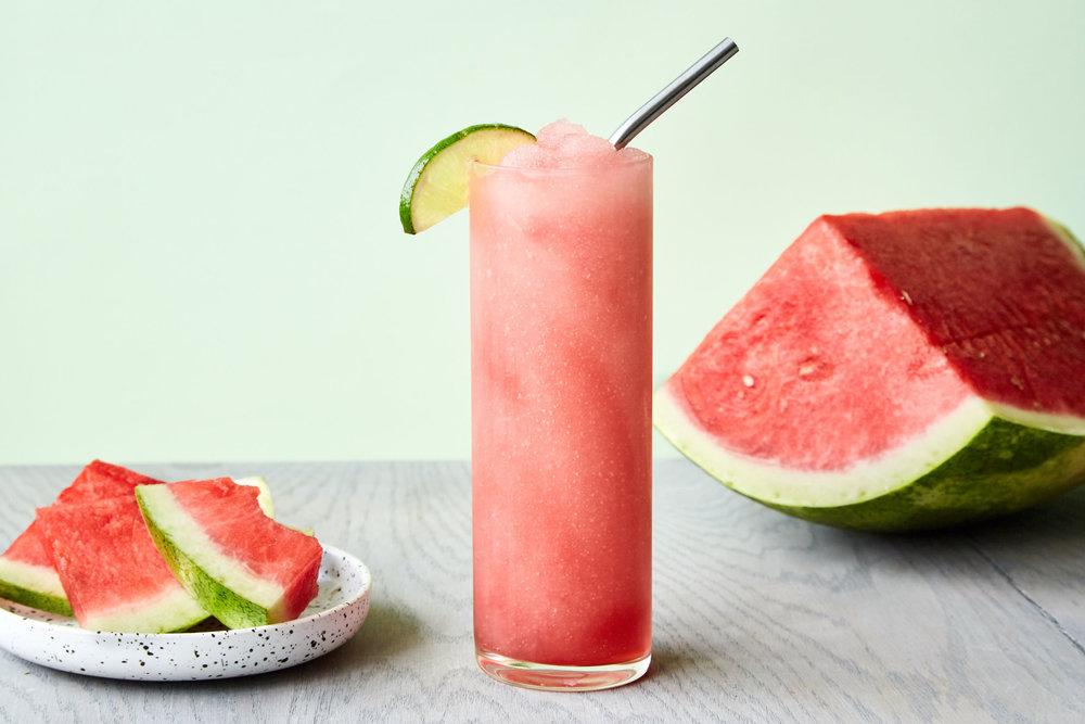 Frozen Watermelon Diablo drink in a tall glass with fresh watermelon.