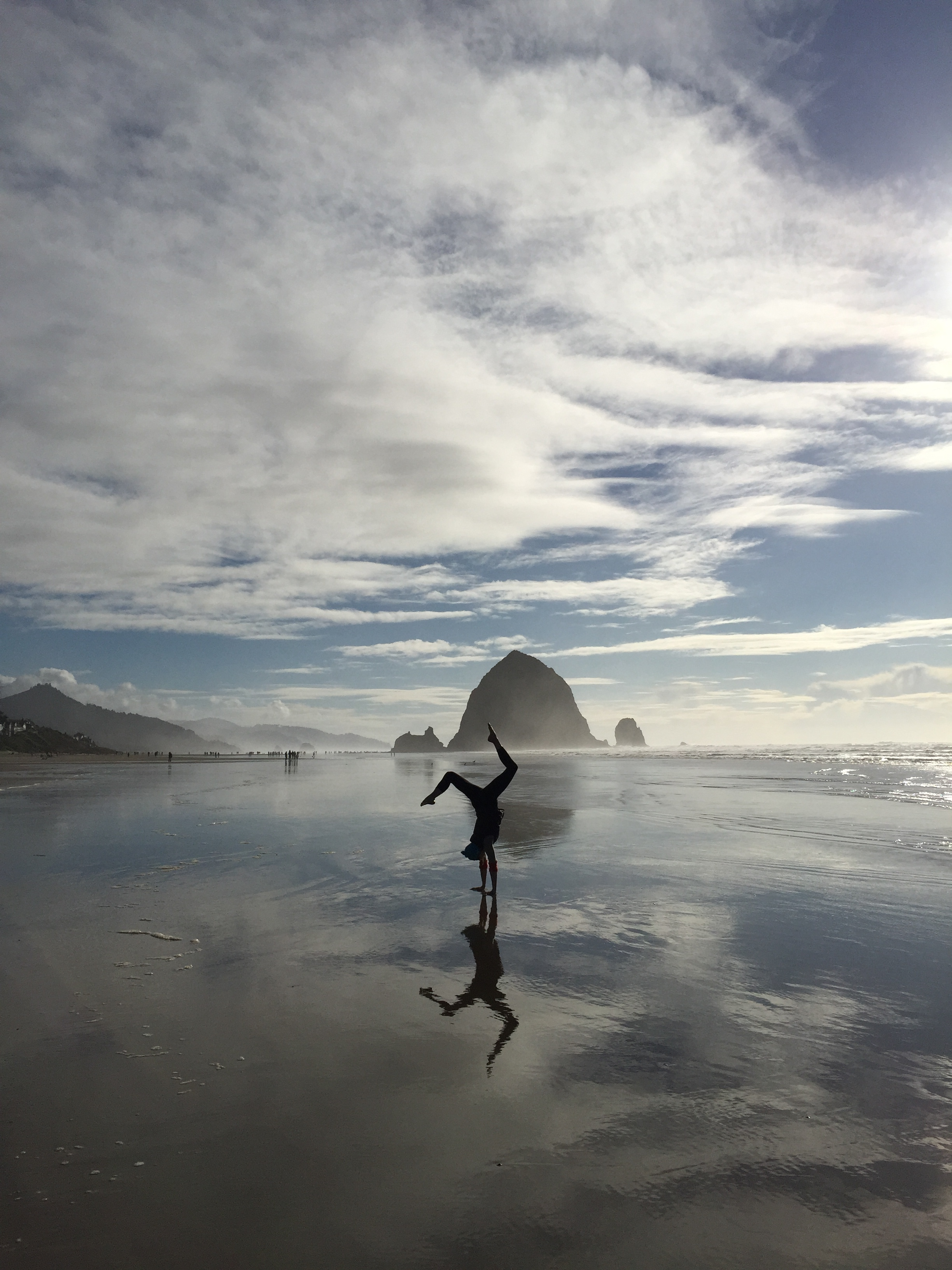 Yoga in front of Haystack Rock on Canon Beach, Oregon