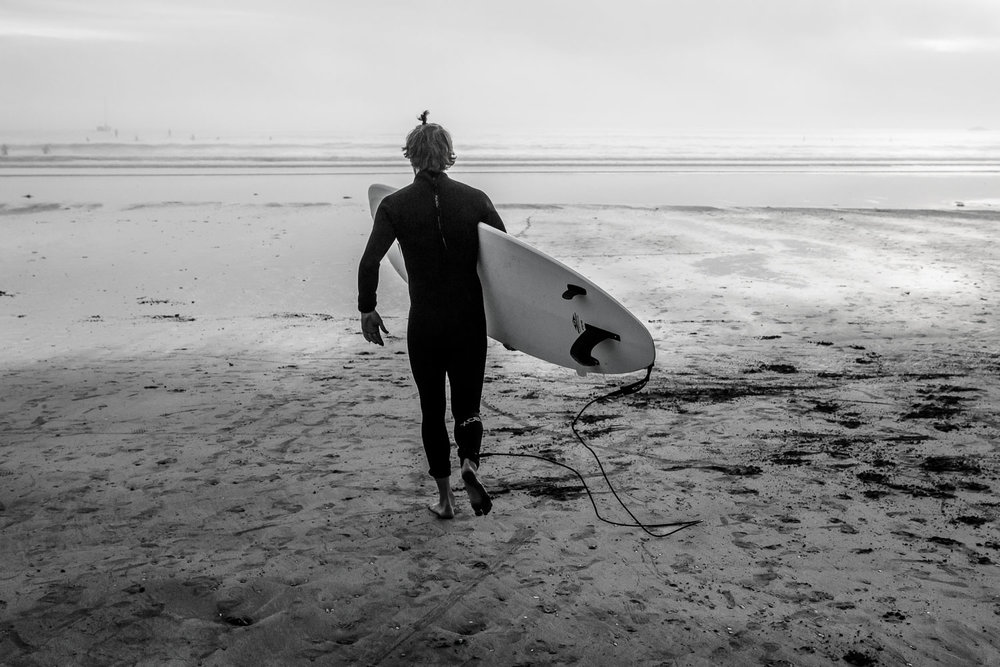 Black and white photo of a surfer at Cox Bay Beach in Tofino, Summer 2017
