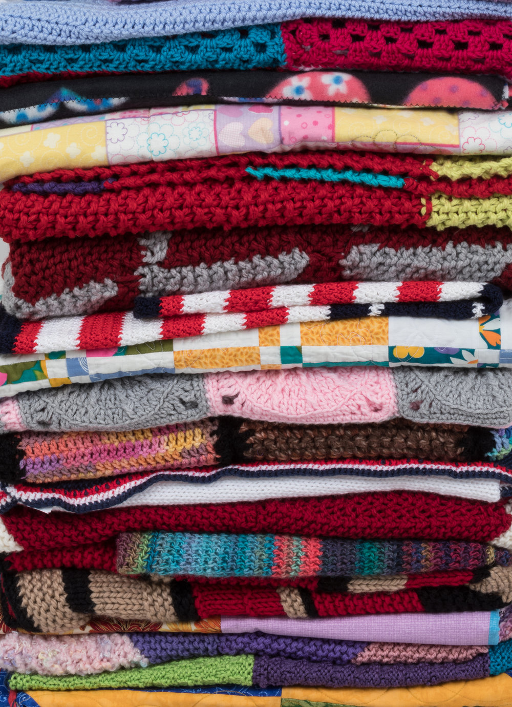 (IMAGE DESCRIPTION: A gigantic pile of blankets of various kinds: knit, crochet, quilted, and maybe woven. Different patterns represented. Different colors present.)