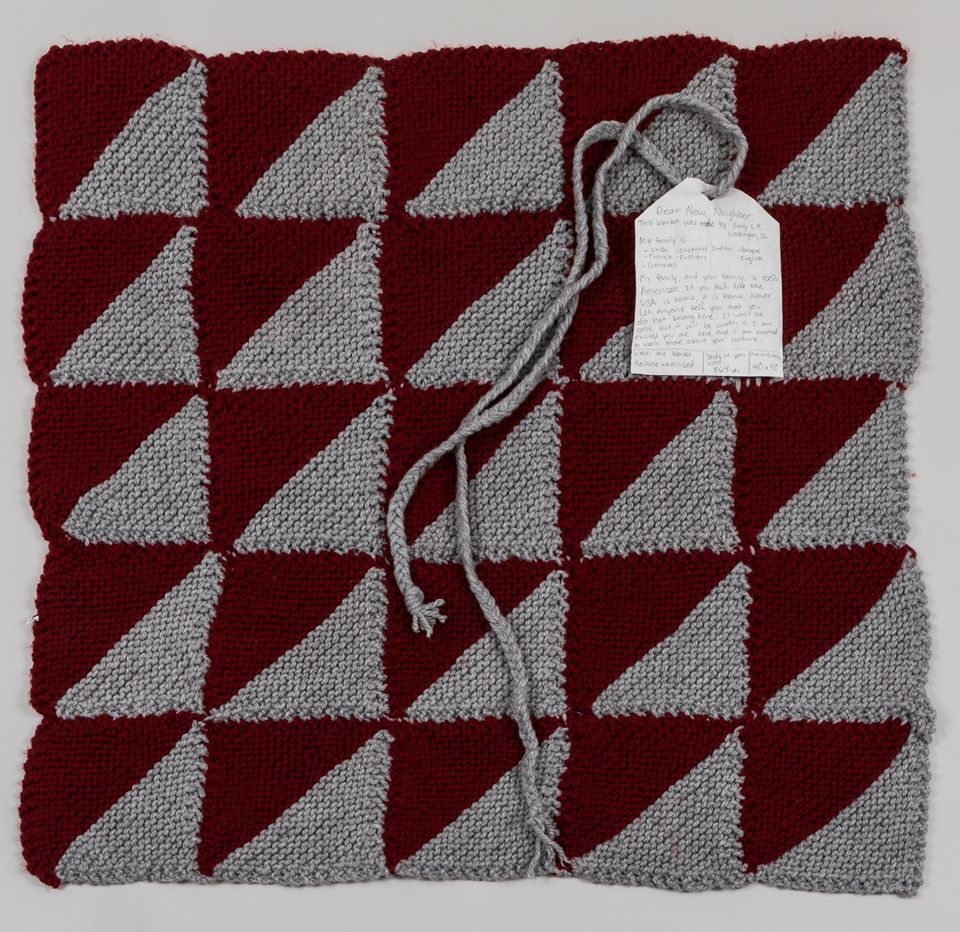 "(IMAGE DESCRIPTION: Welcome Blanket no. 00008  is a 5X5 gray and red repeated half square triangle pattern comes from Atlanta, GA with a note of welcome:  ""My family, and your family, is 100% American. If you feel like the USA is home, it is home. Never let anyone tell you that you do not belong here. It won't be easy, but it will be worth it. I am excited you are here, and I am excited to learn more about your culture."" )"