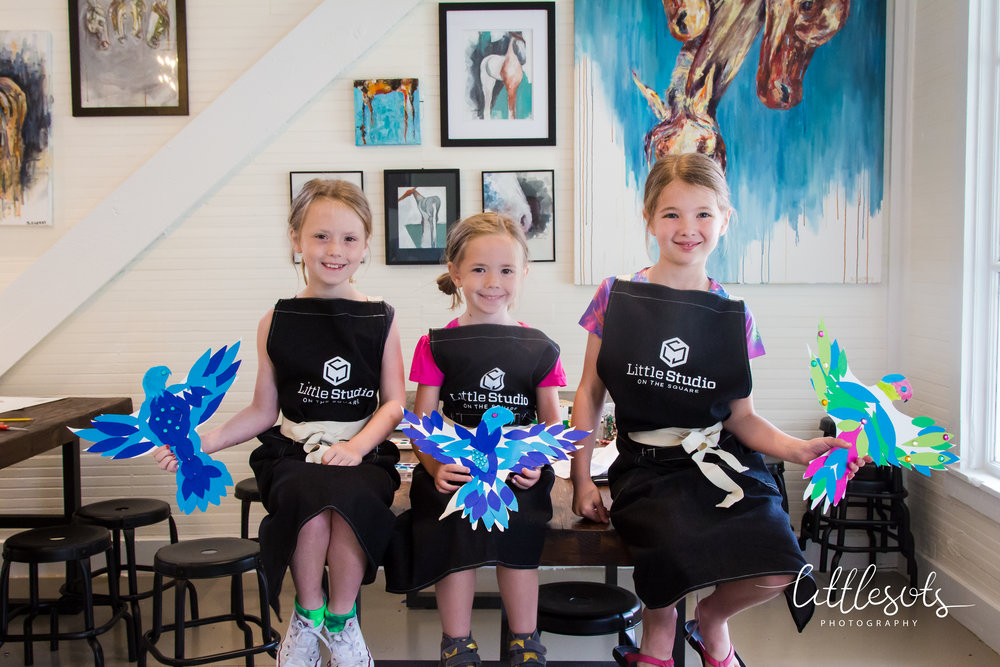 3 young painters show off their hard work.