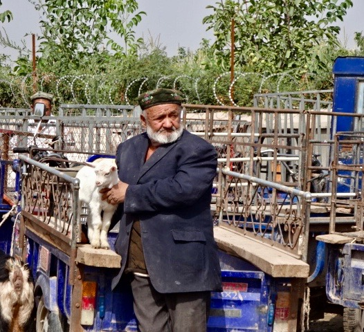 Qighur man with baby goat      -