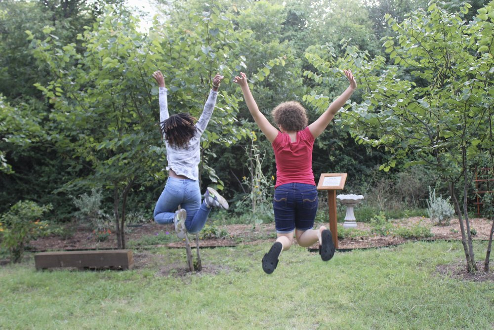 Wheeler House Kids Jumping in Butterfly Garden