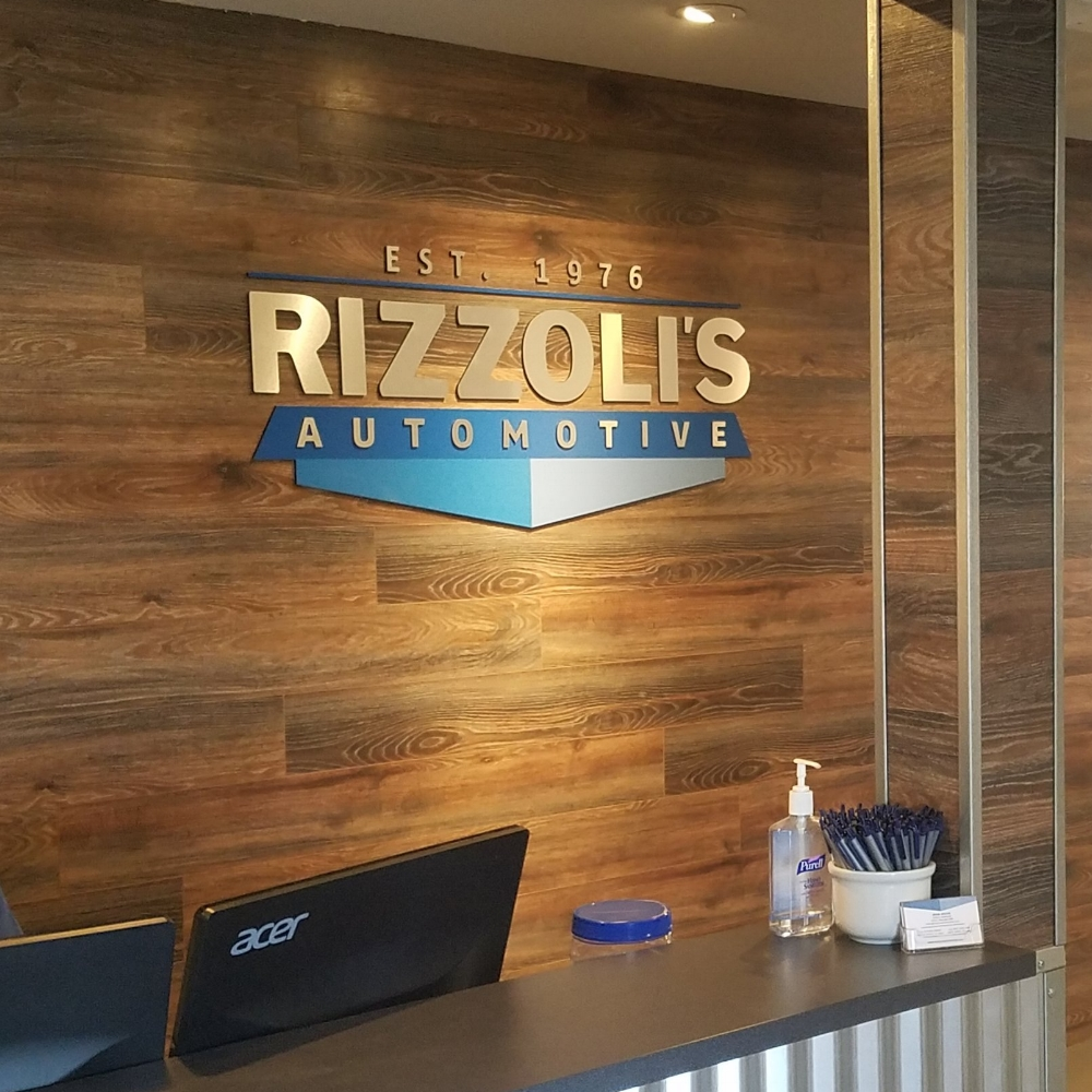 FEBRUARY 2018   Rizzoli's Automotive now has a layered, interior acrylic logo sign in their reception areas at both locations - SLO and Santa Maria. This is a combination of metal lam on acrylic and printed blue vinyl on acrylic. Metal lam is a great way to achieve an interior metal look without the weight and cost of actual aluminum. Check out the amazing remodeled showrooms the next time you need an oil change!