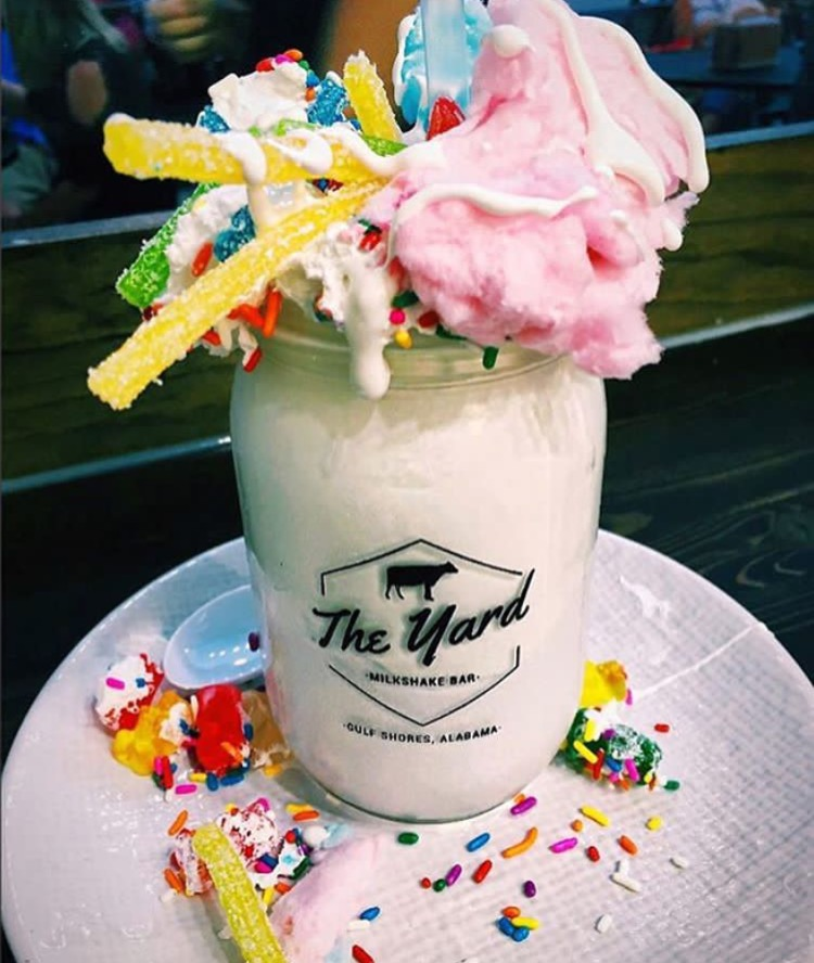 The Mermaid Cotton Candy Ice Cream, topped with sour straws, cotton candy and whipped cream, vanilla icing dipped jar.