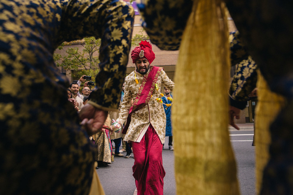 indian wedding groom dances during baraat outside the ritz carlton in charlotte NC