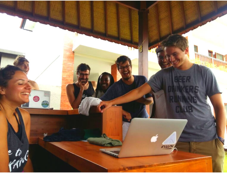 Group of smiling young professionals looking at laptop on outdoor terrace