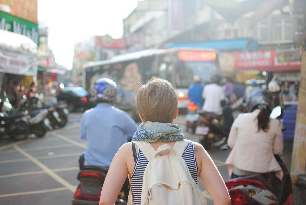 Female backpacker walking through streets in Vietnam