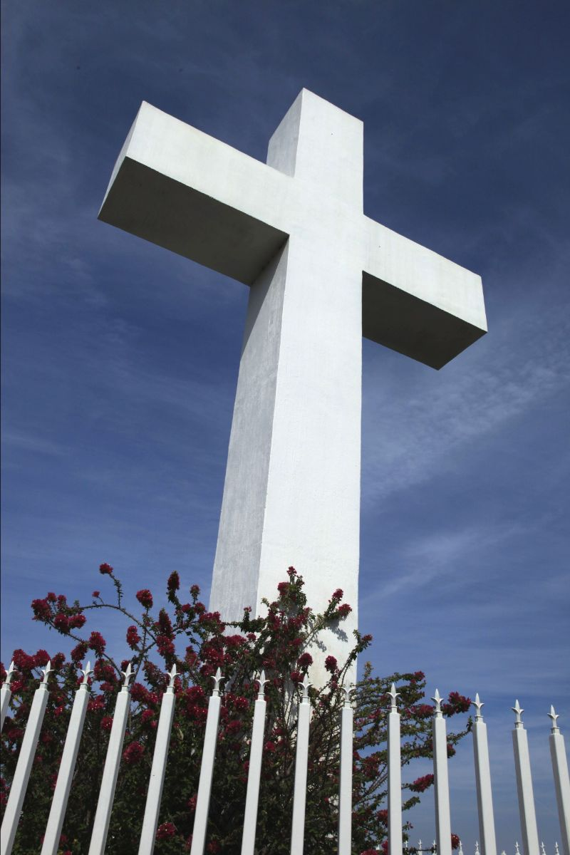 Big white cross with flowers at the bottom