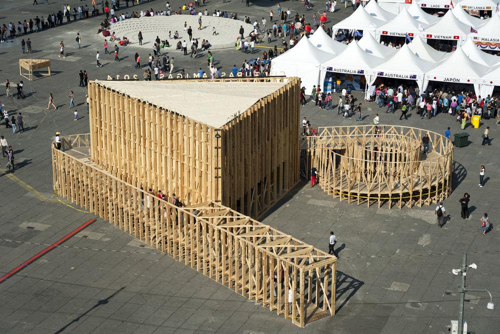 PABELLÓN DE LA CIUDAD DE MÉXICO-FERIA DE LAS CULTURAS AMIGAS 2014   Ciudad de México  Cliente: PRODUCTORA  Obra: 2014  Estructura espacial de madera estructural, de 8m de altura, construida para el zócalo de la ciudad de México. Fue diseñada para ser prefabricada de tal manera que su instalación se lograra realizar en 5 días. El sistema de apoyo a la base se concibió por gravedad sin requerirse anclaje alguno al piso existente. Obra ganadora del premio MCHAP.emerge 2014/2015.