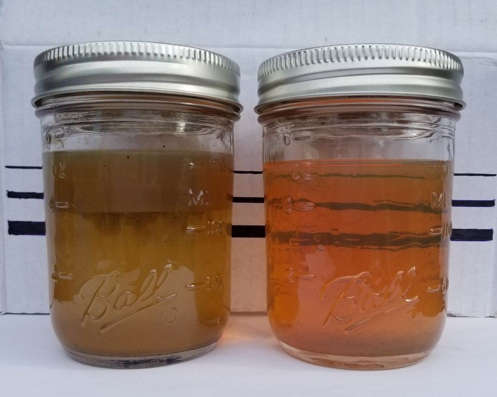 The jar on the left shows a sample from the bottom of a tank with sediment and water on the bottom, a layer of bacteria and debris in the middle, and old fuel with more particulate matter on top. The sample on the right is from the bottom of the same tank after fuel polishing.