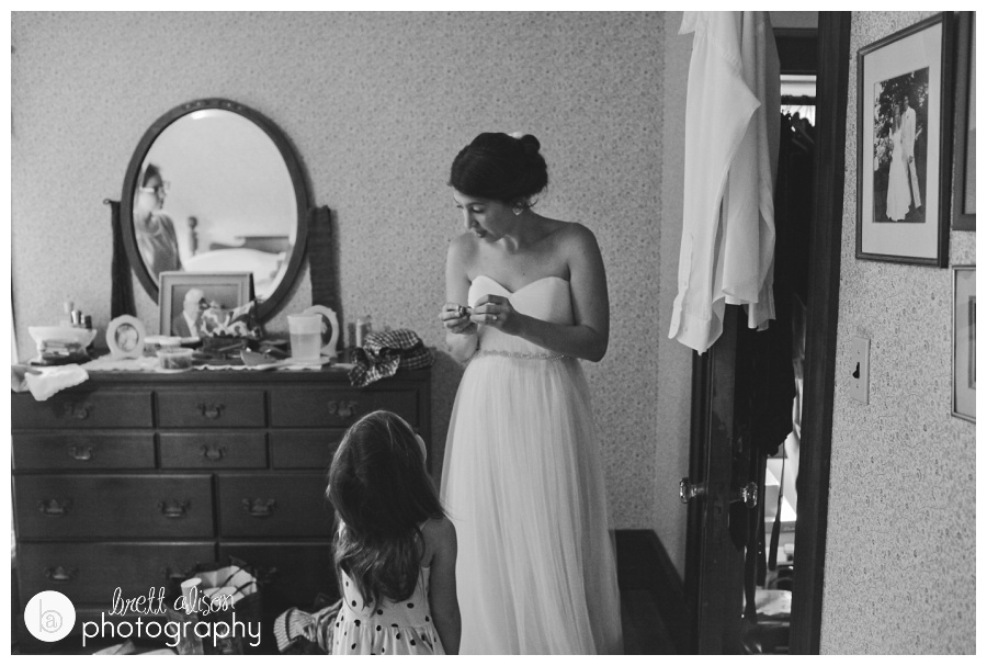 Lots of little details in this photo, that I didn't even notice until after I had shot it and was editing. Kate and Geoff got married at her grandparents' home, and she got ready in their bedroom. On the edge you can see a family wedding photo, in the mirror, Kate's sister is watching her get ready and in the foreground is her niece, looking up at her. Just like all these eyes are on the bride on her big day!