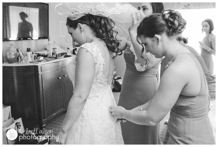 "I love capturing some of the whirlwind energy that goes on during the ""getting ready"" phase of the wedding. There were lots of bridesmaids helping out, and I like the reflection of one friend watching in the reflection of the TV."