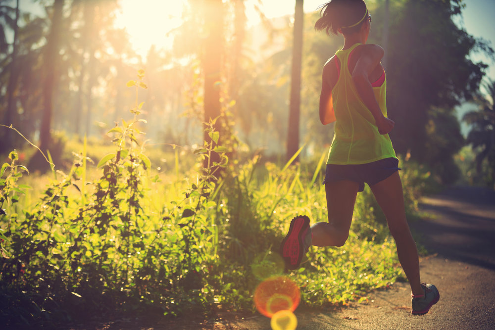 Woman trail running sunshine