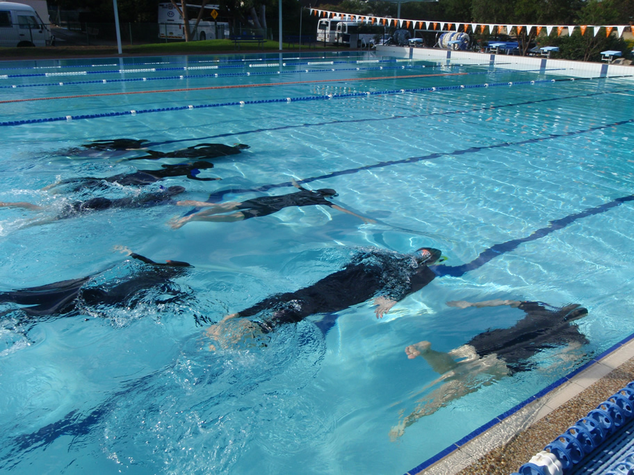 Students compare effectiveness of swimming without equipment with wearing equipment.