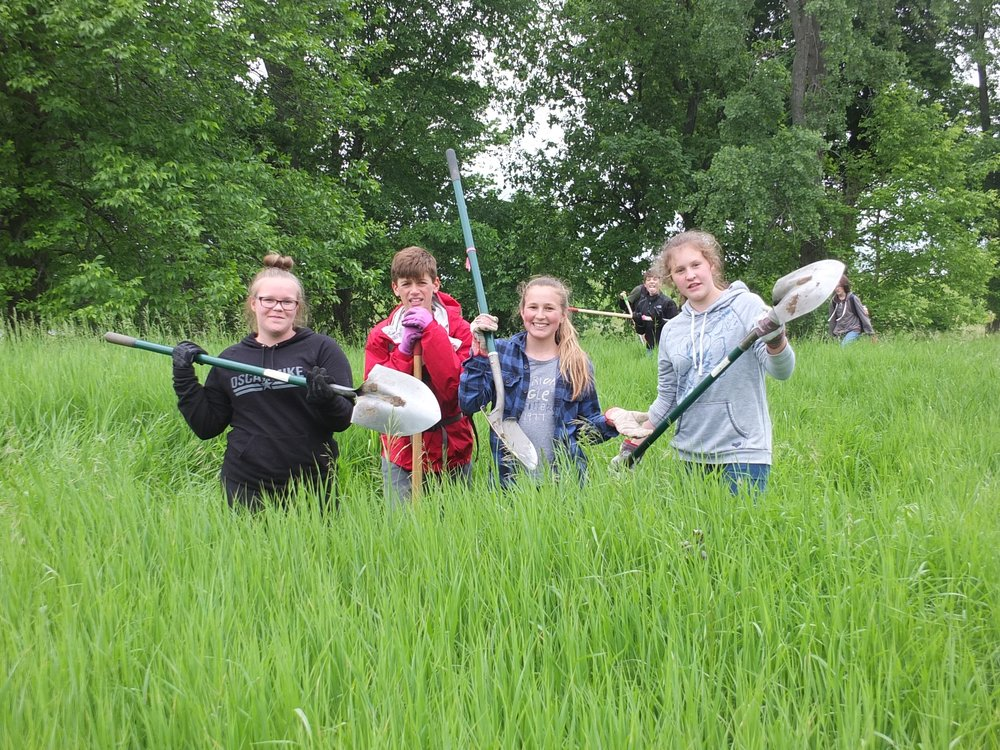 Students from Folsom Education and Community Center participate in an annual service learning day, digging up invasive wild parsnip at Round Pond Natural Area.