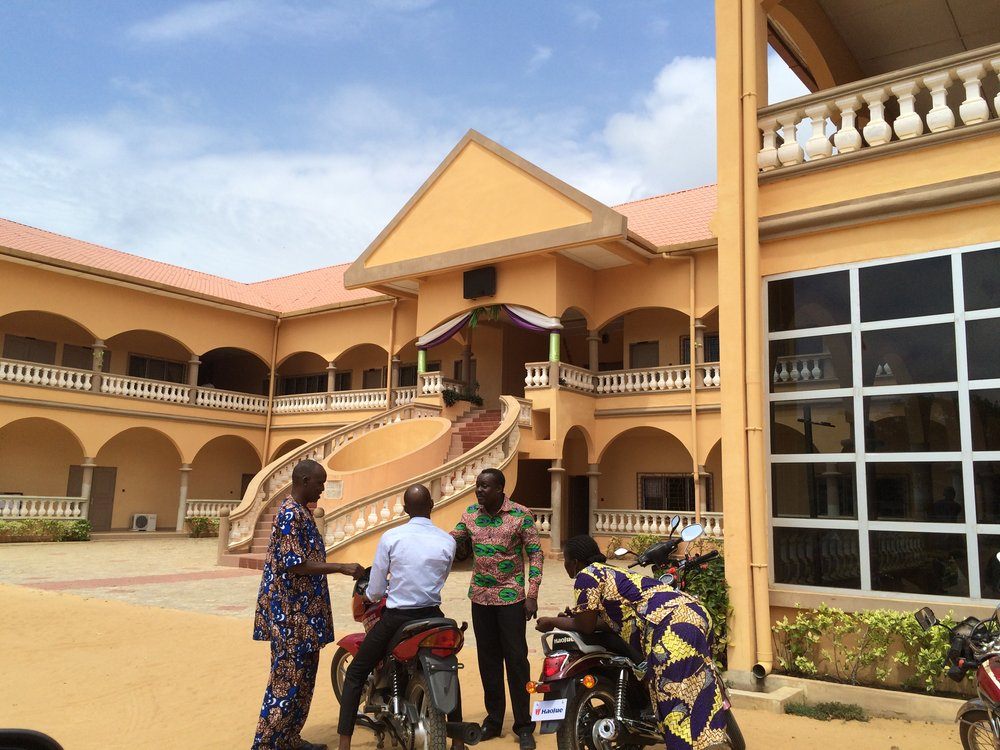 Municipal tax collectors report to their boss outside City Hall in Ouidah, Benin 2015