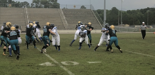 "Running back Cheri ""Mimi"" Gantt gets great blocks as she breaks through the Pumas defense"