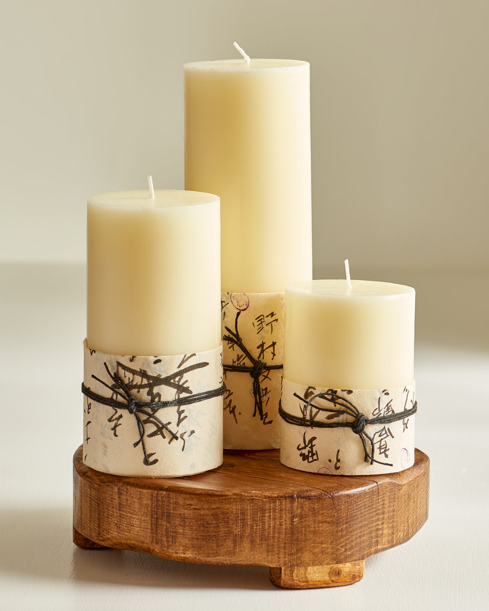 Ivory pillar candles wrapped in antique Chinese paper, from $9