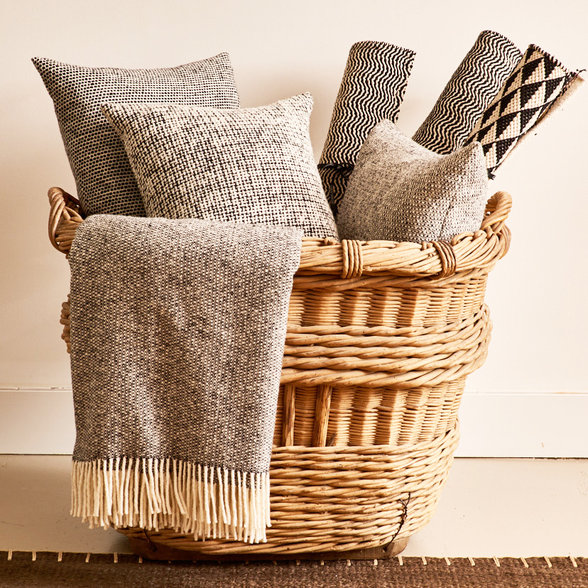Irish wool tweed throws, pillows, from $175, geometric cotton throw rugs, from $30, antique French laundry basket, $600