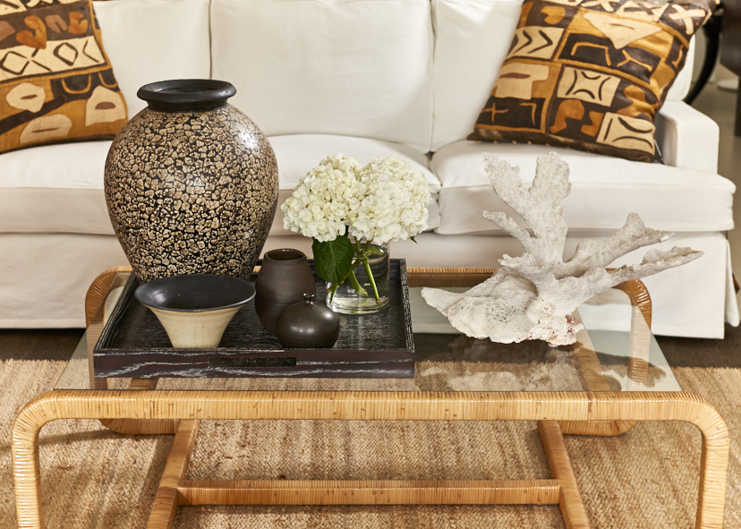 Rattan, glass cocktail table, c. 1970, $1800,  Duane Modern Greenwich sofa from $6500, vintage Kuba cloth pillows, $350, eggshell vase, Indonesia, $750, coral $450, oak tray (in two finishes), $500