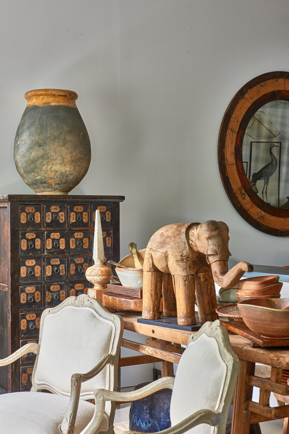 Pair of French olive oil urns.  $3200, papier-mâché elephant mold, Indonesia $1200, antique mirror, $2400, pair, French bergères $4500