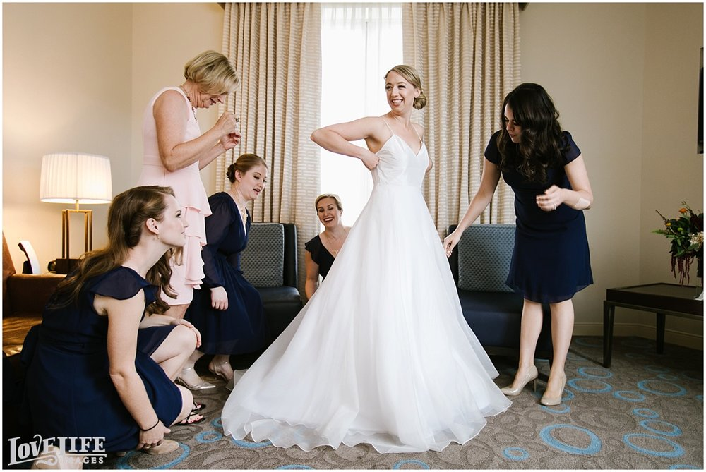Longview Gallery DC Wedding bride putting on dress.jpg