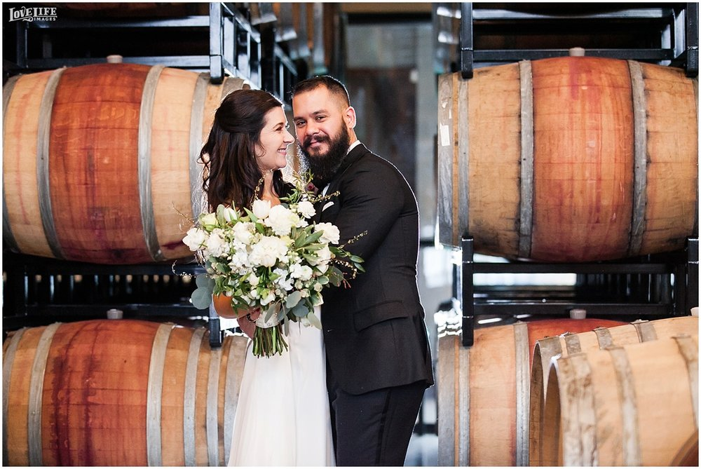 District Winery DC Wedding bride and groom in wine barrels portrait.jpg
