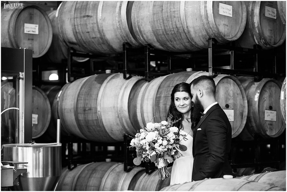 District Winery DC Wedding bride and groom portrait with wine barrels.jpg