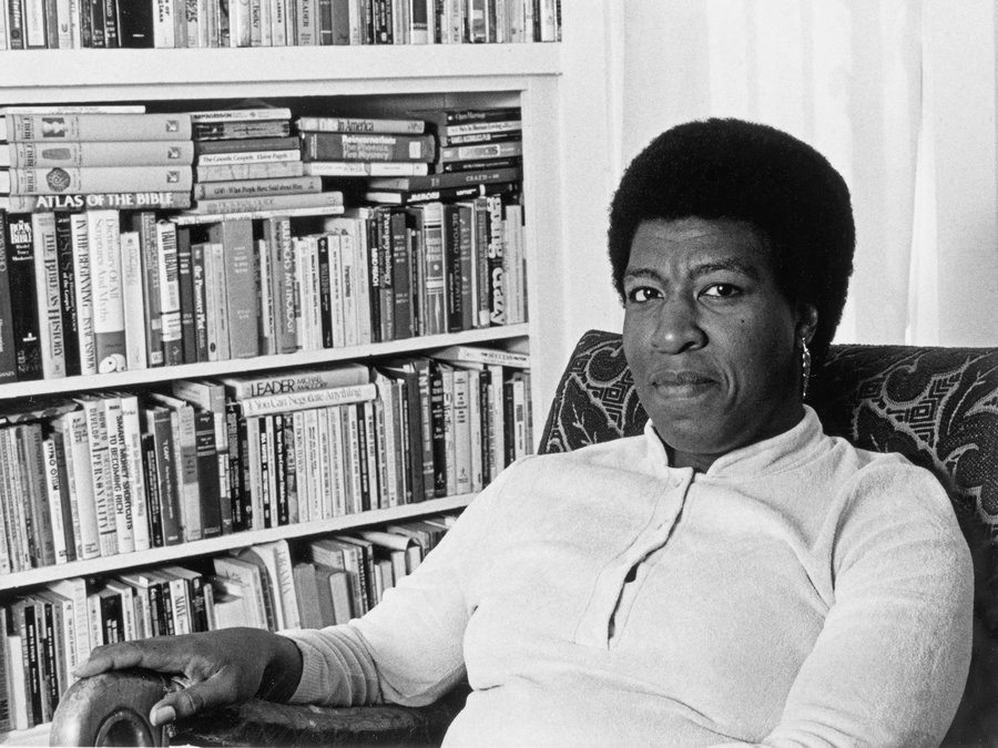 Photograph of Octavia E. Butler seated by her bookcase, 1986.