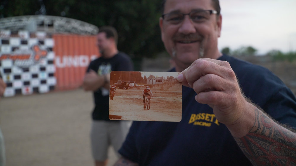 Mark Darcy holding up a picture of him racing on the first day of races at Orange Y BMX. Still from Generation BMX footage.