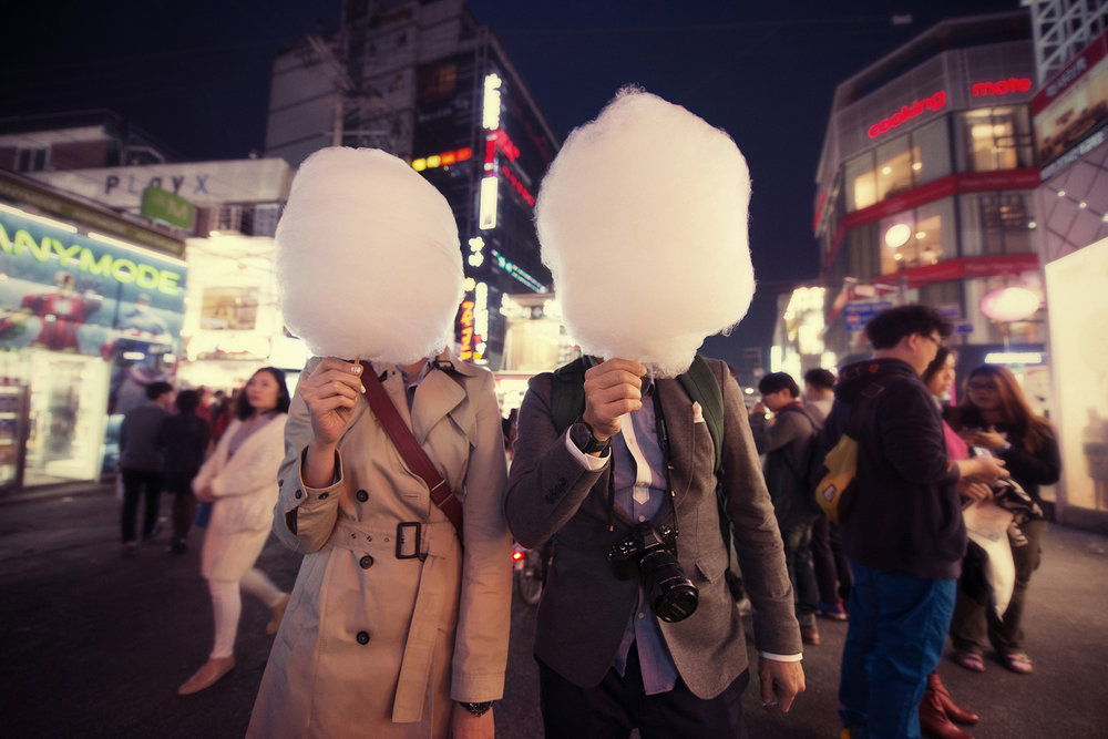 Mike and Bernie enjoying their cotton candy that's bigger than their face in the vibrant night streets of Seoul
