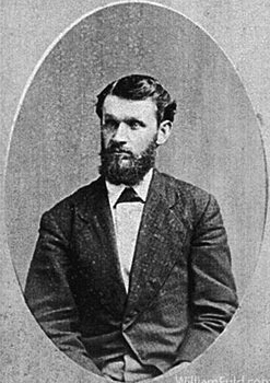 A photo of Elijah Bond. He has a beard and is dressed in a black suit