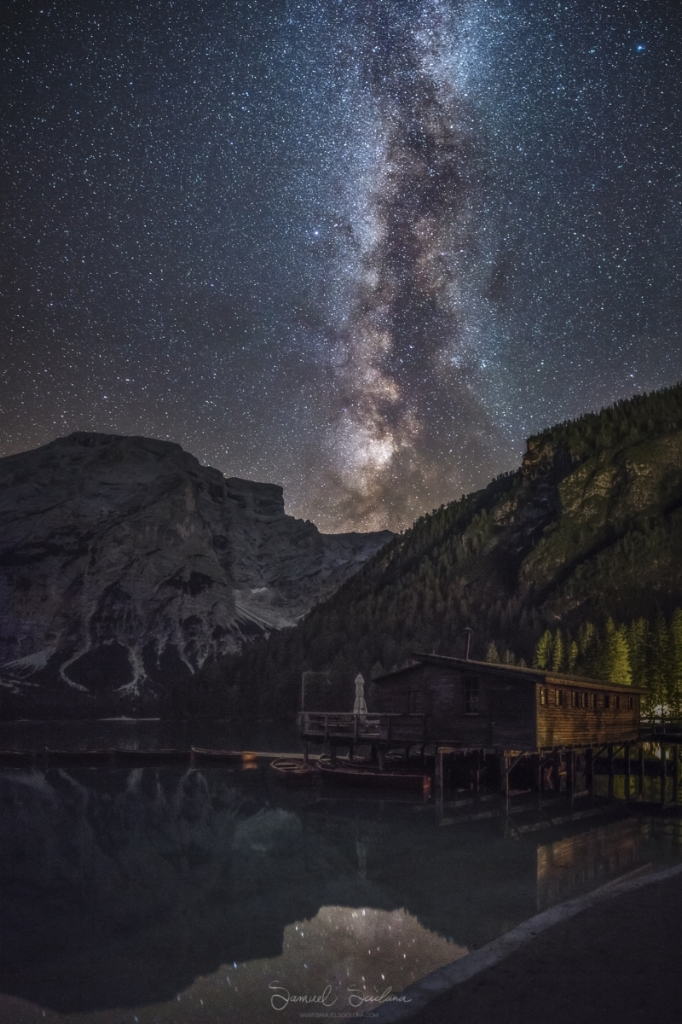 A 4 image vertical panorama showing the Milkyway over the boathouse at Lago di Braies