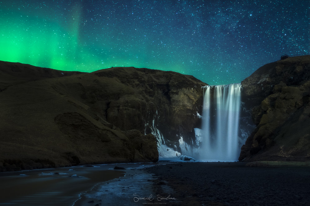 Skogafoss by night with the Northern lights dancing in the sky above.