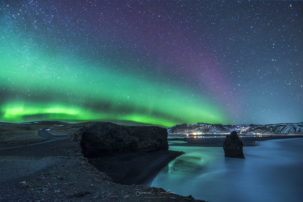The Northern Lights dancing over the Arnardrangur Sea Stack.