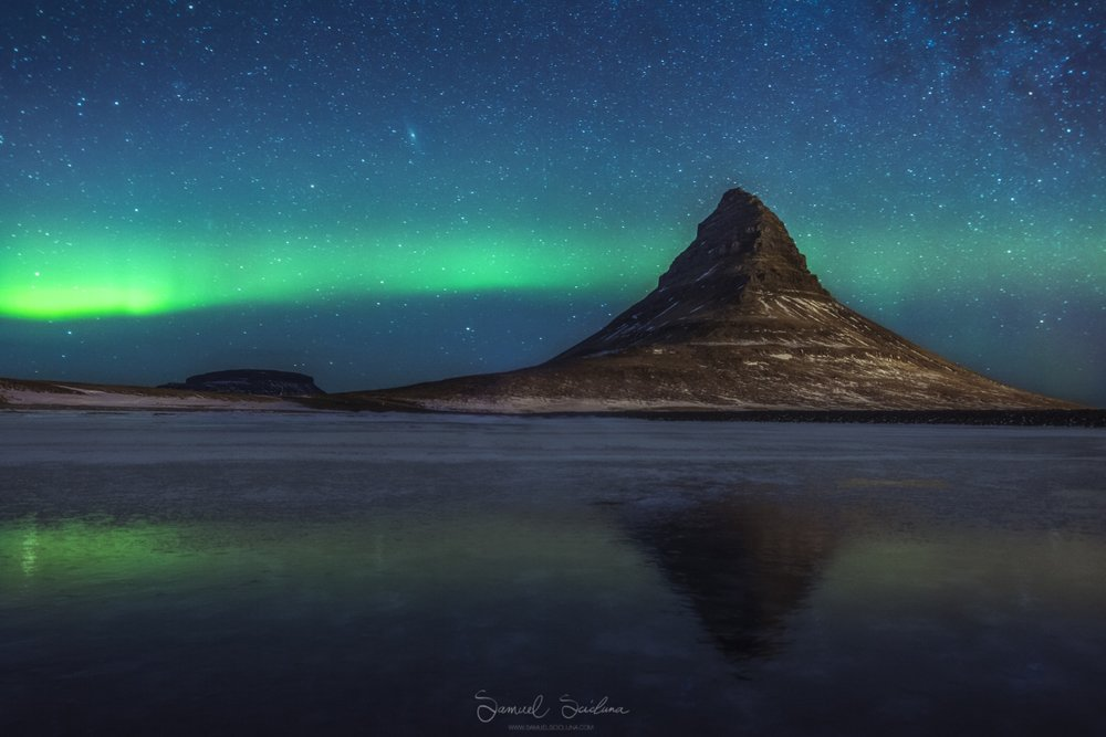 The Northern Lights above Kirkjufell reflecting in a frozen lake.
